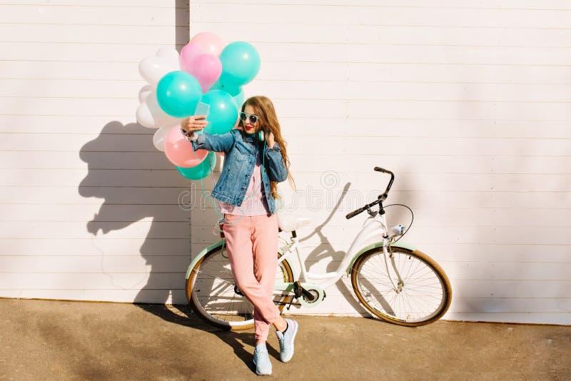 Hellång stående av flickan i stilfulla rosa flåsanden och grov bomullstvillomslaget som framme gör selfie av den vita cykeln bj?d arkivfoton