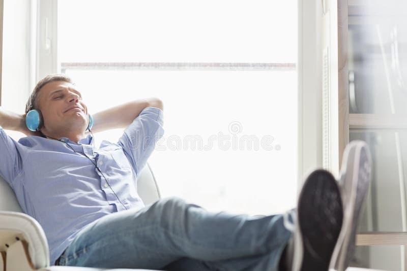 Hellångt av den avkopplade medelåldersa mannen som hemma lyssnar till musik arkivbilder
