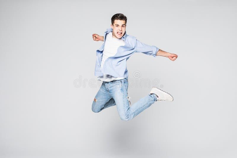 Hellångt foto av den roliga mannen i tillfällig t-skjorta och jeans som kör eller hoppar i luft som isoleras över vit bakgrund royaltyfria bilder