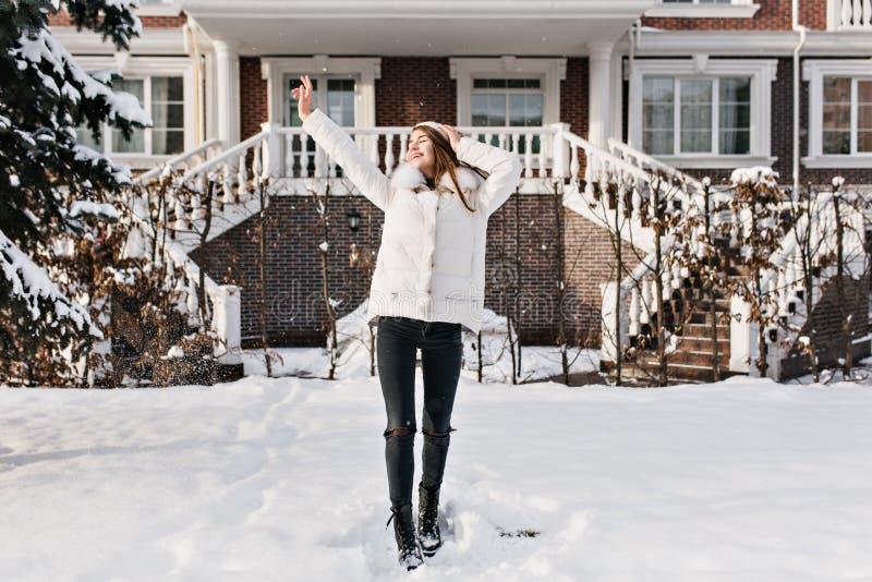 Hellångt foto av den slanka unga kvinnan i varm stilfull kläder som tycker om vinterhelg Utomhus- stående av att fascinera royaltyfri foto