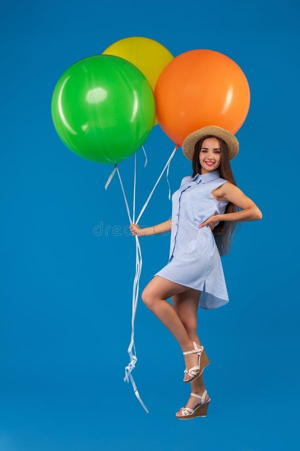 Hellångt skott av att le den unga kvinnan som ser färgrika luftballonger för kamera som och för innehav isoleras över blått arkivbilder
