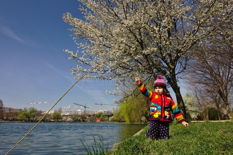 Hell farbiges Mädchen täuscht vor, unter einem blühenden Baum zu fischen stockbilder
