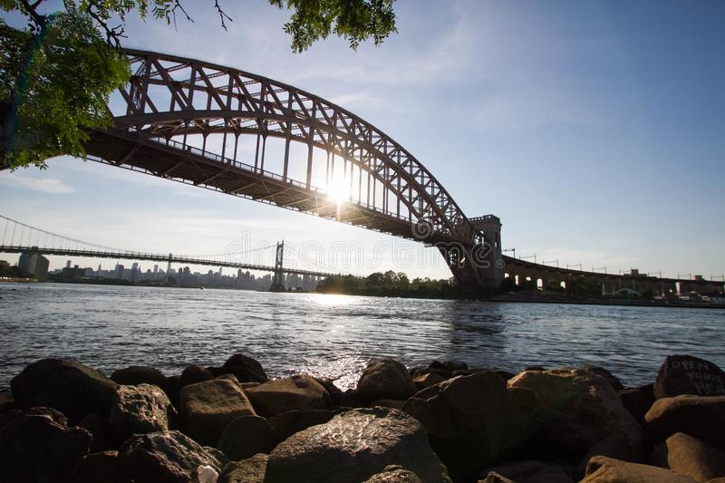 The Hell Gate Bridge, rocks and the sun reflect on the river. New York royalty free stock photos