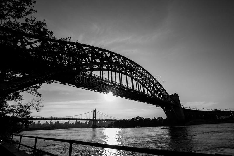 The Hell Gate Bridge and the sun reflect on the river in black and white style. New York royalty free stock photography