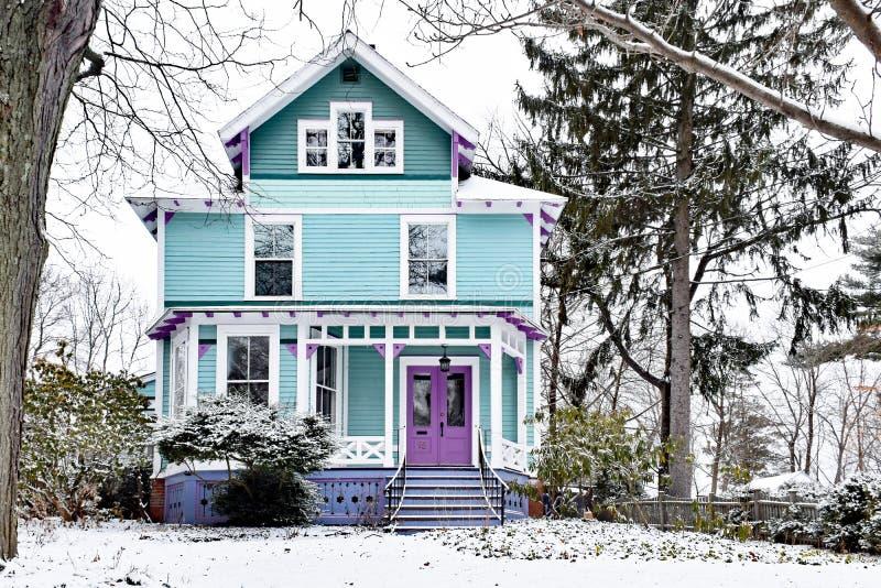 Hell gemaltes viktorianisches Haus bedeckt im Schnee lizenzfreie stockbilder