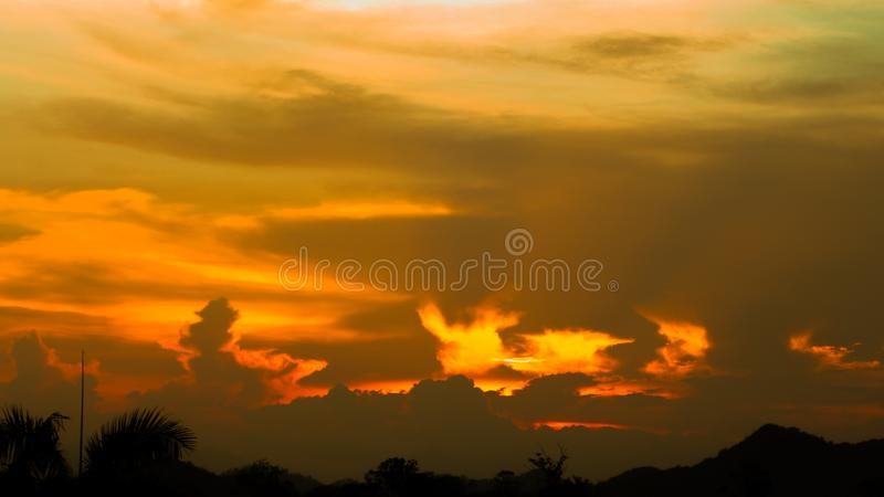 Hell in Heaven colorful Clouds Silhouette blue Sky Background Evening golden sunset with rays of light shining through clouds. Hell in Heaven colorful Clouds stock photo