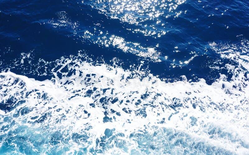 Hellblaue Tiefseeoberfläche mit weißer Gischt, Wellen und Scheinen stockfotos