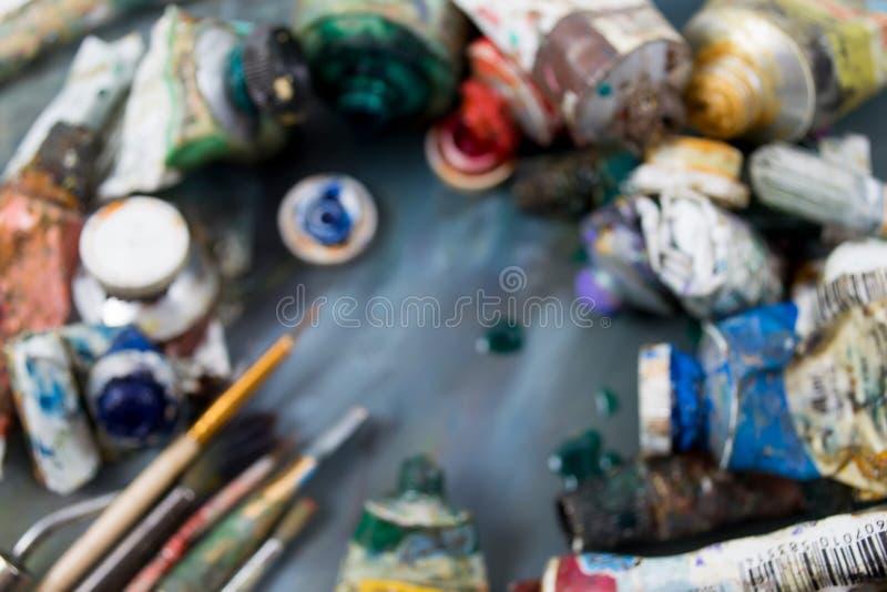 Helle Ölfarben in einem Rohr auf einer schmutzigen Palette Malt gebräuchlich entziehen Sie Hintergrund lizenzfreie stockfotos