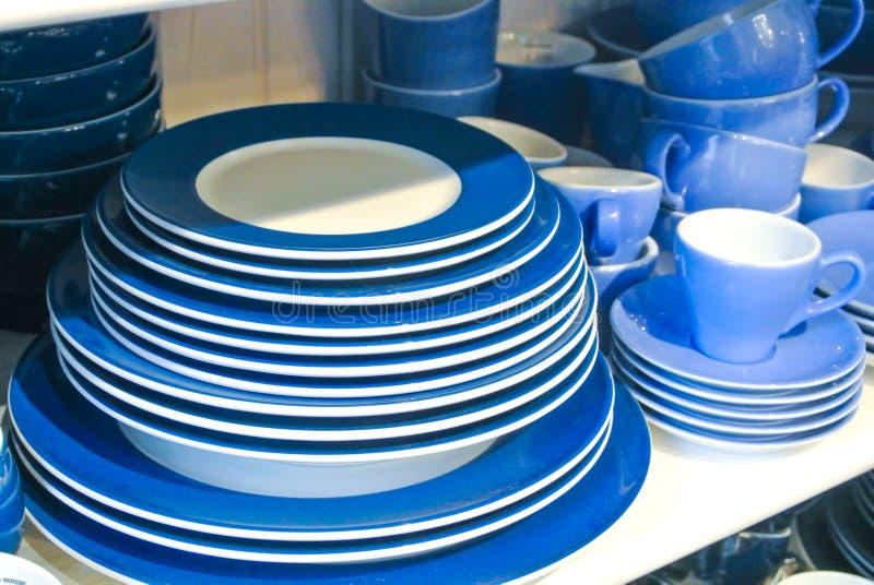 Helle blaue und weiße Teller, Platten und Schalen, die auf Weiß stehen stockfotos