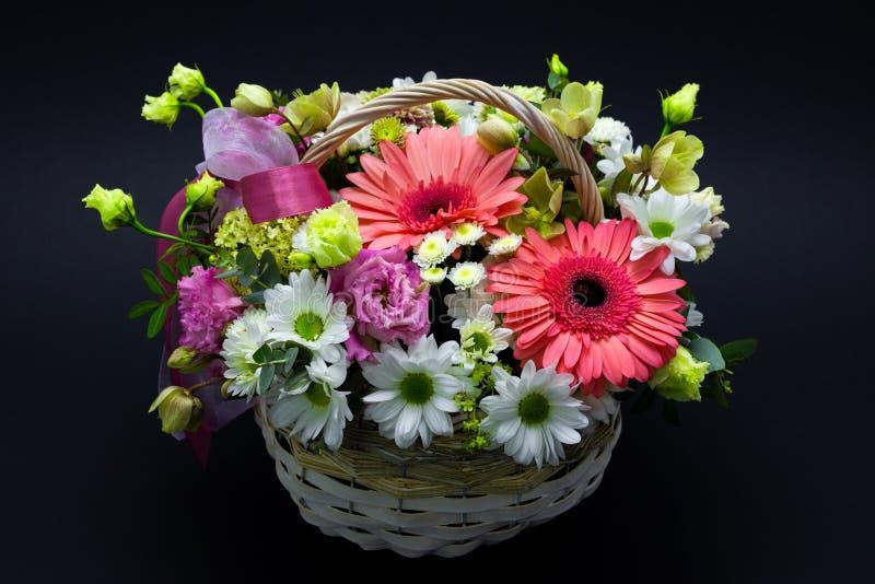 Helle Blumenanordnung in einem weißen Korb auf Blumen eines dunklen Hintergrundes in einem Weidenkorb stockfotografie