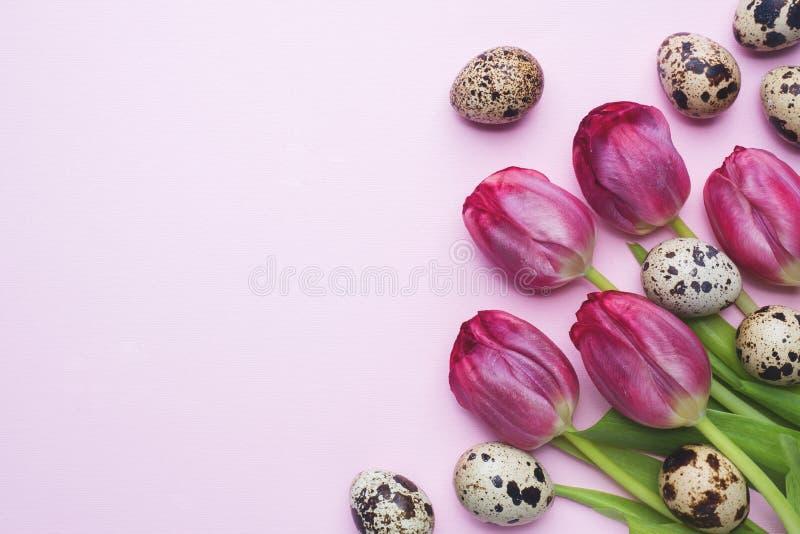 Helle Blumentulpen und Wachteleier auf Farbhintergrund Frühlings- und Ostern-Feiertagskonzept mit Kopienraum stockfoto