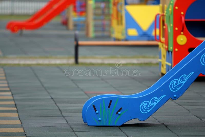 Helle bunte Dias auf Kindertagesstättenspielplatz mit Weichgummibodenbelag am hellen sonnigen Sommertag Kindertätigkeiten und stockbild