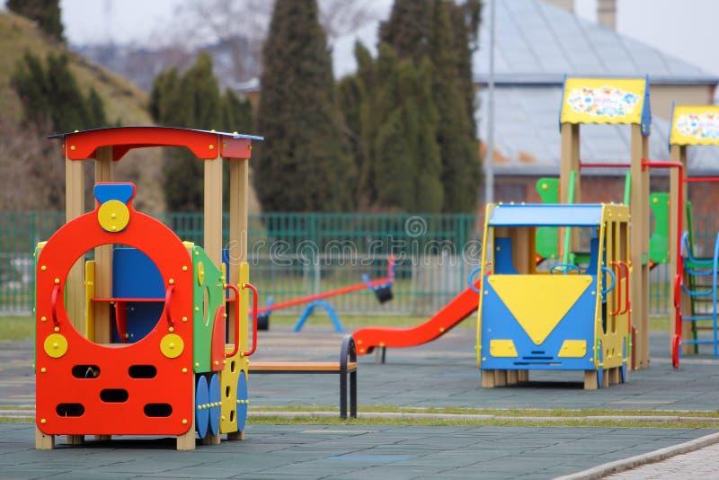 Helle bunte große Spielzeugautos auf Kindertagesstättenspielplatz mit Weichgummibodenbelag am hellen sonnigen Sommertag Perfekter lizenzfreies stockfoto