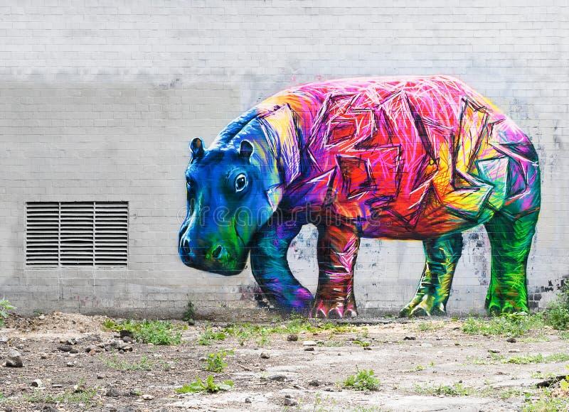 Helle farbige Nilpferdgraffiti auf einer grauen Backsteinmauer lizenzfreie abbildung