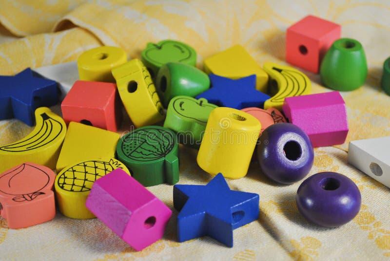 Helle farbige Perlen des Holzes der verschiedenen Formen für die Kreativität der Kinder Stern, Apple, Ananas lizenzfreies stockfoto