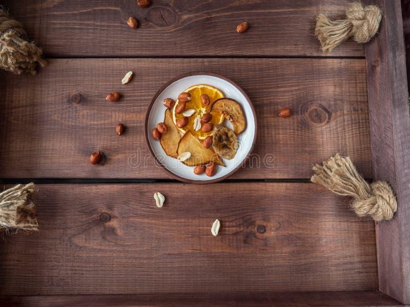 Helle Fruchtchips und Erdnussn?sse f?r einen hellen Imbiss auf einem h?lzernen rustikalen Beh?lter stockfotos