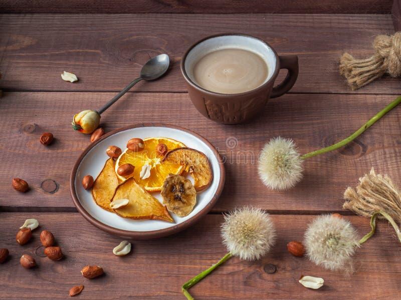 Helle Fruchtchips und Erdnussnüsse für hellen Morgenkaffee mit Milch auf einem hölzernen rustikalen Behälter lizenzfreies stockbild