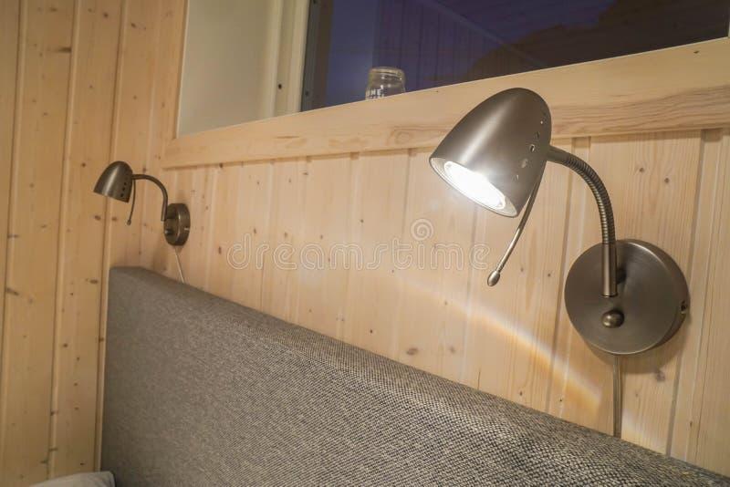 Helle Glühlampelampe an der Kopfende des Schlafzimmers im Hotel stockfotografie