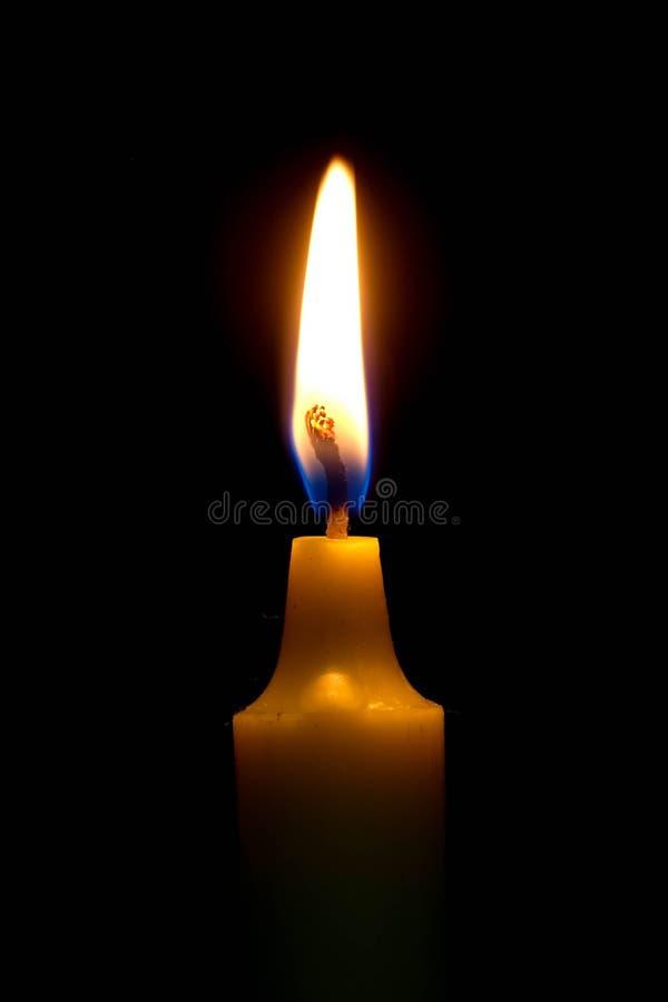 Helle Kerze, die hell auf schwarzem Hintergrund brennt lizenzfreie stockbilder