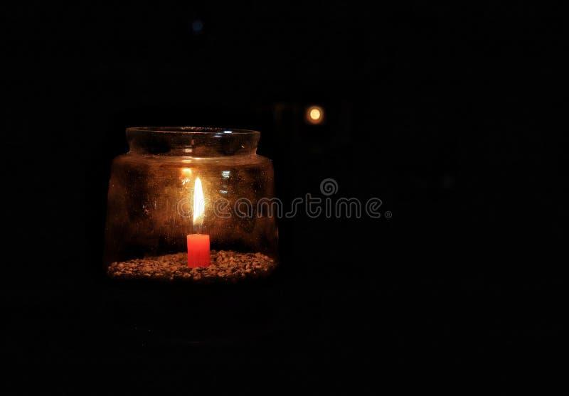 Helle Kerze innerhalb des Glases, das in die Dunkelheit glüht stockfoto
