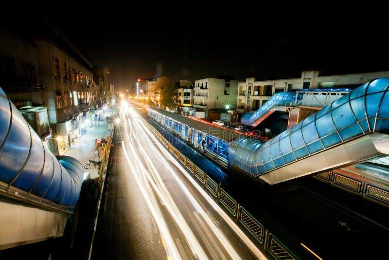Helle Linien der Bewegungsunschärfe von hetzenden Autos auf der hellen Straße der Nachtstadt stockfoto
