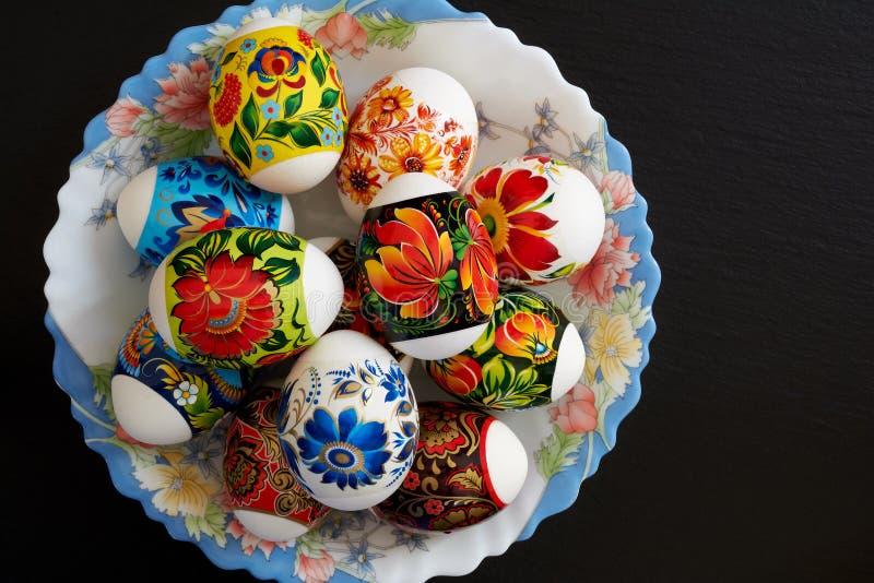 Helle mehrfarbige Ostereier mit Blumenmuster in der Platte auf dunklem Hintergrund Symbol des religi?sen Feiertags lizenzfreie stockbilder