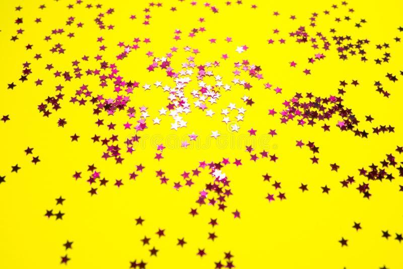 Helle rosa Sterne auf hellem gelbem Hintergrund stockfotos