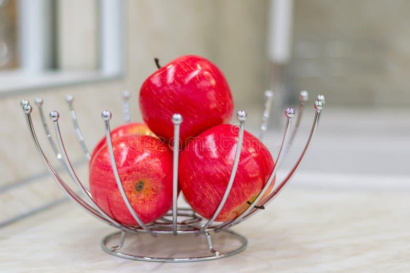Helle rote Äpfel im ursprünglichen Metallvase Küchentisch Komfort im Haus lizenzfreies stockbild