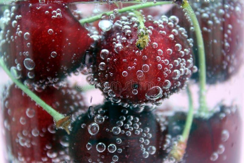 Helle rote frische Kirschflöße im funkelnden Wasser in einem Glas und mit Blasen bedeckt stockfotografie