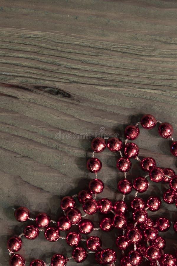 Helle rote metallische Perlen auf rustikaler Holzoberfl?che stockfotos