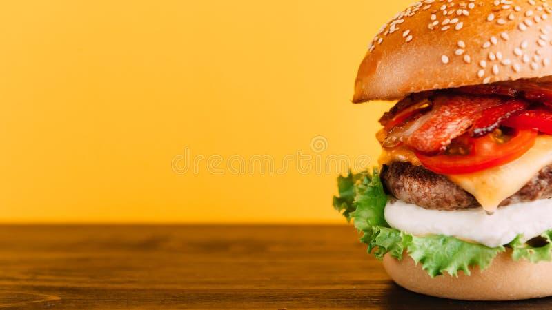 Helle saftige appetitanregende Burger mit Hieben, Käse, marinierten Gurken, Tomaten und Speck stockbilder