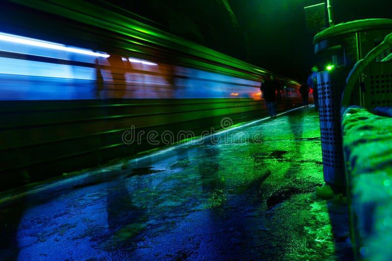 Helle Spur des Zugs, Zug in der schnellen Unschärfe, Reisenachthintergrund, Leute im verbreiteten Eilhaus lizenzfreie stockfotografie