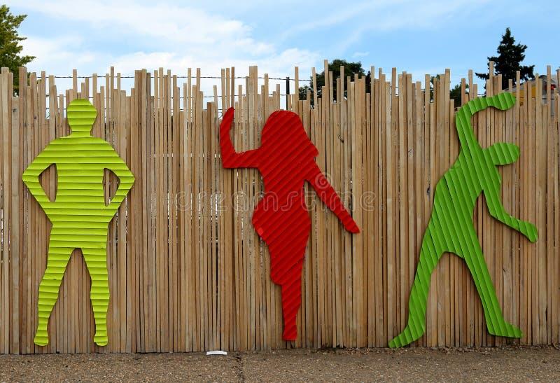 Helle tanzende Schattenbilder auf dem vorübergehenden Zaun nahe folgender Galerie auf Colfax-Allee in Denver lizenzfreies stockfoto