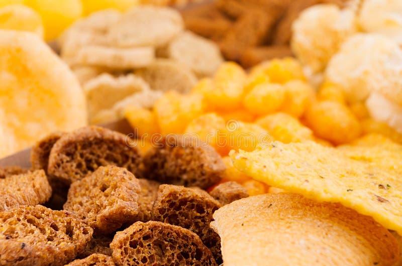 Helle würzige Snacksammlung - Popcorn, Nachos, Kartoffelchips, Croutons, Mais haftet als Hintergrund, Nahaufnahme stockfoto