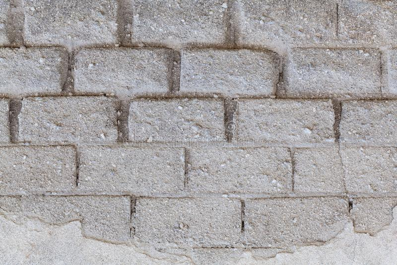 Helle weiße Backsteinmauer mit großem Block stockfotos