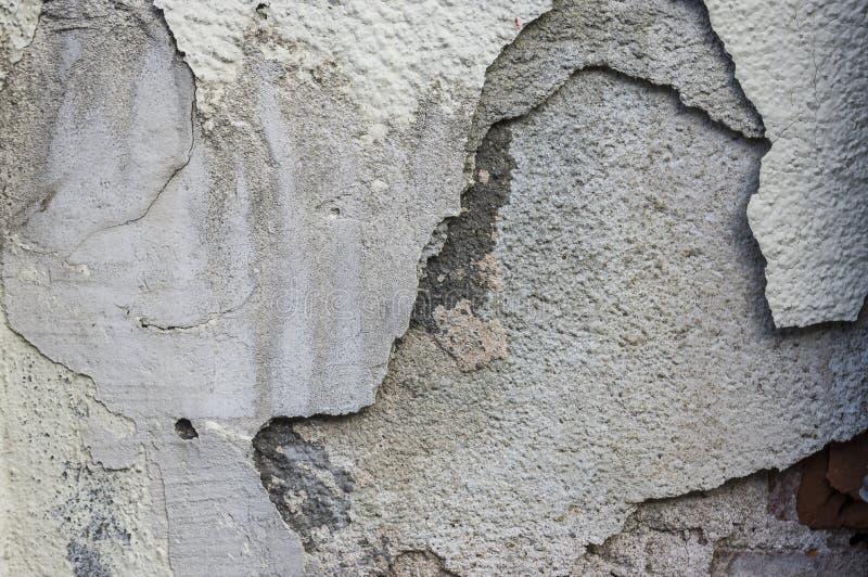 Hellend pleister met barsten in verscheidene lagen op reno van de huismuur stock afbeeldingen