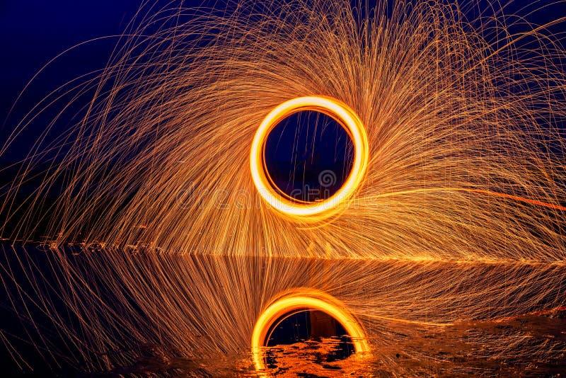 Heller Anstrich Pyrotechnische Anzeige nachts mit der Reflexion des Wassers stockbild