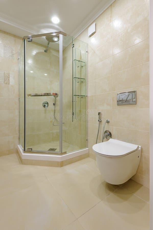 Heller Badezimmerinnenraum mit Glasdusche und Toilette stockfoto