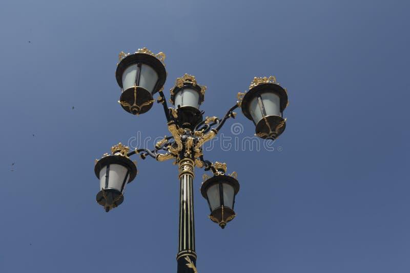 Heller Beitrag mit blauer Himmel-Hintergrund Straßenlaterne der Weinlese im Freien Viktorianische große Laterne der Roheisen-Lamp lizenzfreies stockbild