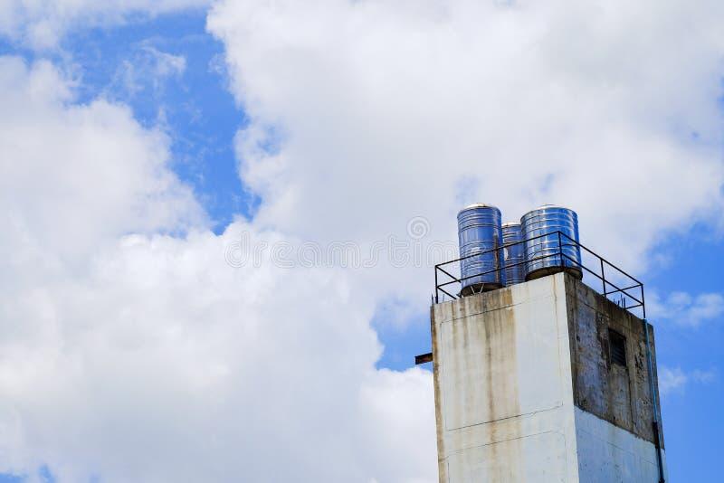 Heller blauer Himmel mit Wolken- und Wasserbehältern stockfoto