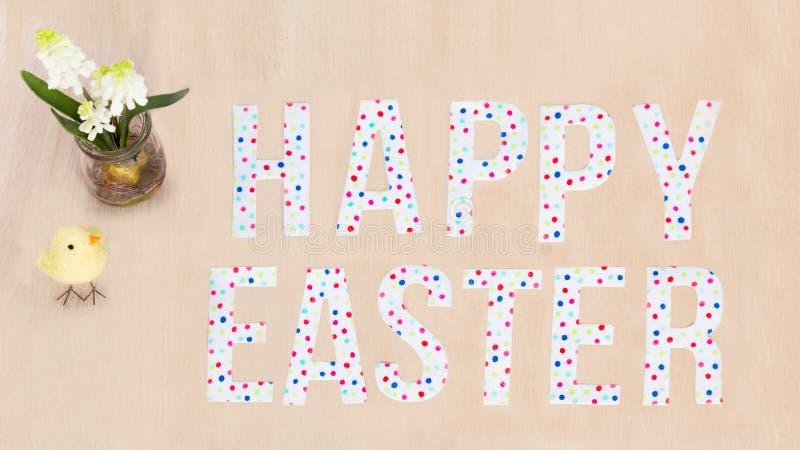 Heller bunter glücklicher Ostern-Text, Küken, Blumen auf hölzernem backgr lizenzfreie stockbilder