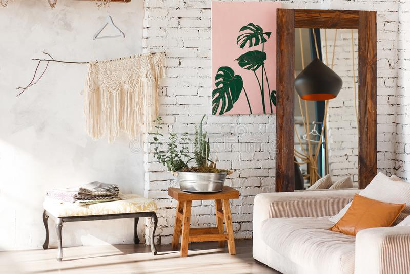Heller Dachbodeninnenraum mit weißen Backsteinmauern, Spiegel, modernes Licht, Sofa, Dekor lizenzfreie stockbilder