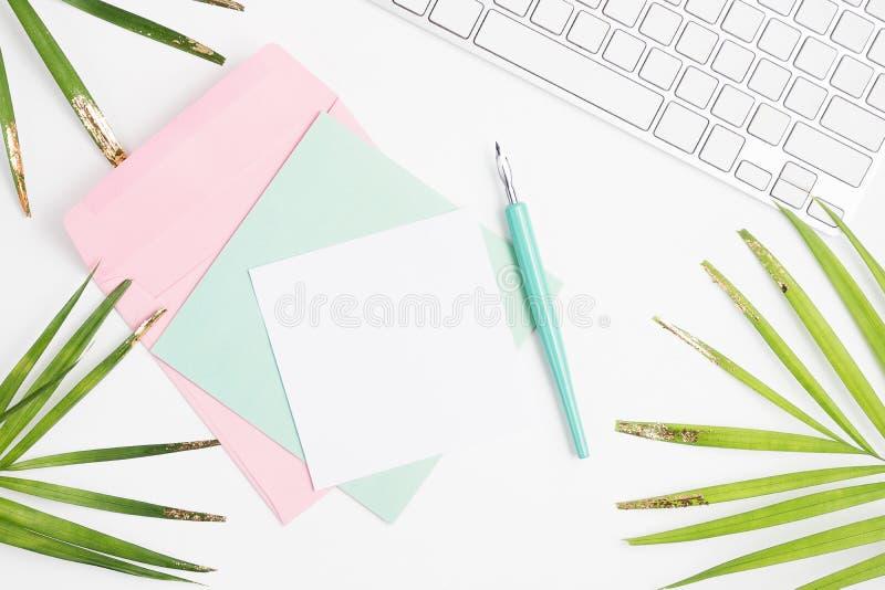 Heller Ebenenlage-Modespott oben: weiße Tastatur, goldene Palmblätter, bunte Karten, Umschlag und Federhalter auf weißem Hintergr stockbild