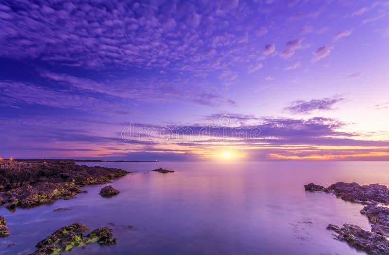 Heller erstaunlicher heller Sonnenuntergang und felsiges seacost stockfotografie