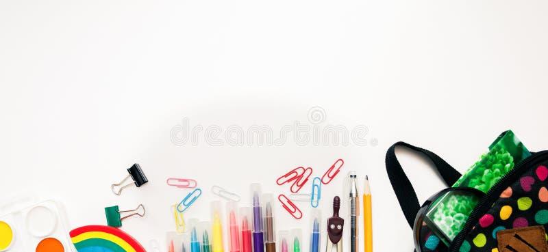 Heller farbiger Rucksack und bunter stationärer Schulbedarf auf weißem Hintergrund, Raum oder flacher Schicht des Textes Konzept  lizenzfreies stockbild