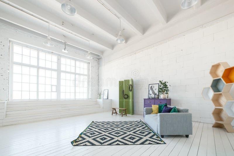 Heller Fotostudio- oder -wohnzimmerinnenraum mit großem Fenster, hohe Decke, weißer Bretterboden, modernes Sofa anderes lizenzfreie stockfotos