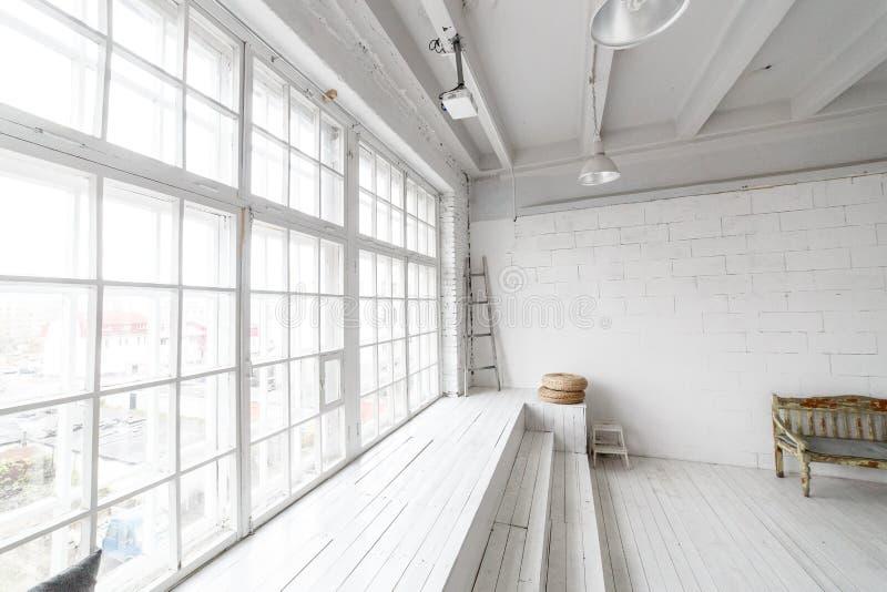 Heller Fotostudioinnenraum mit großem Fenster, hohe Decke, weißer Bretterboden stockbilder