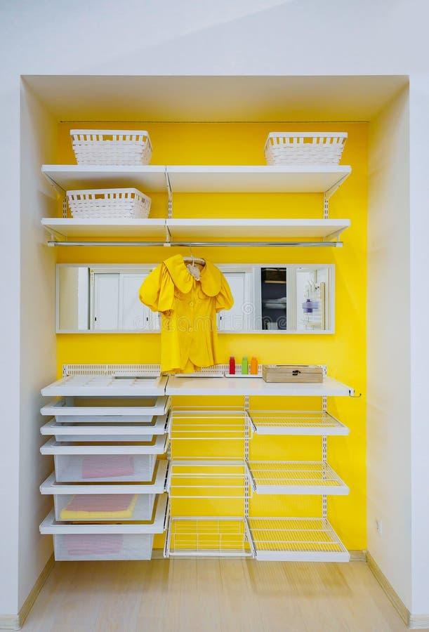 Heller gelber begehbarer Schrank mit Kleidung und Regal, Behälter, boxen zu Hause stockbild