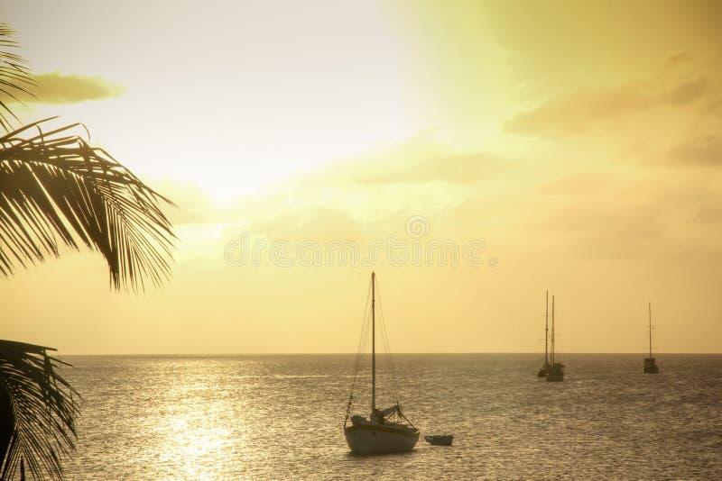Heller gelber Sonnenuntergang mit Segelbooten, Caye-Kalfaterer Belize stockfoto
