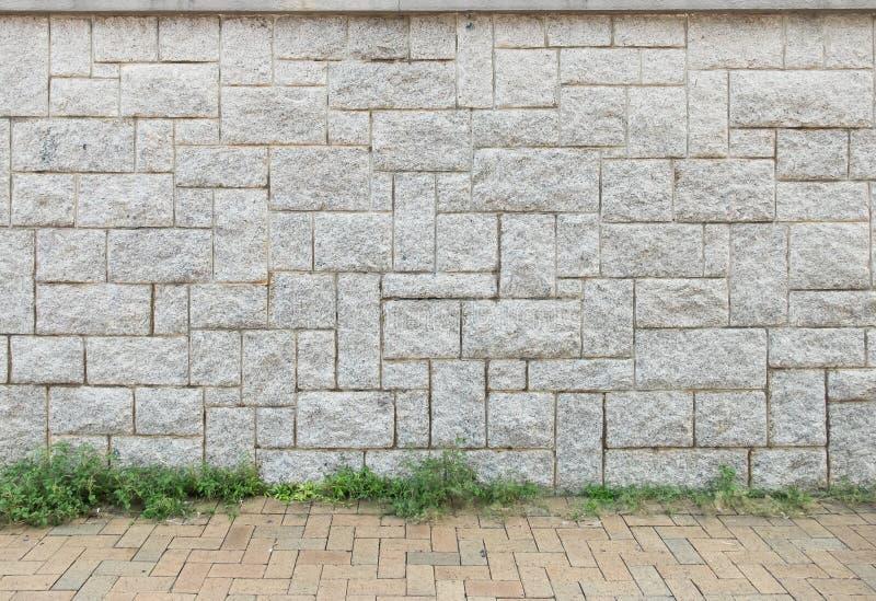 Heller Gray Stone Wall Background Texture mit Brown-Stein-Boden und Gras stockfotos